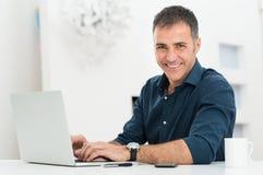 Man som använder bärbara datorn på skrivbordet