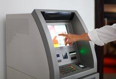 Man som använder bankrörelsemaskinen Fotografering för Bildbyråer