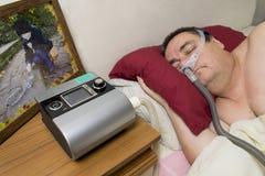 Man som använder CPAP-maskinen och sover maskeringen för behandling av sömn arkivbild
