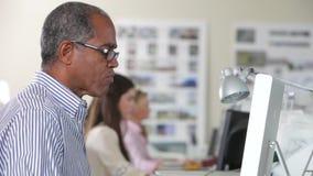 Man som använder datoren på skrivbordet i upptaget idérikt kontor stock video