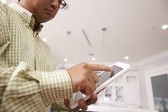 Man som använder den Digital minnestavlan för att kontrollera att tända hemma royaltyfri bild