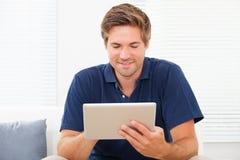 Man som använder den Digital minnestavlan på Sofa At Home royaltyfria foton