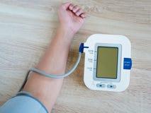Man som använder den digitala blodtryckbildskärmen Arkivbilder