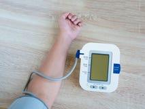 Man som använder den digitala blodtryckbildskärmen Arkivfoto
