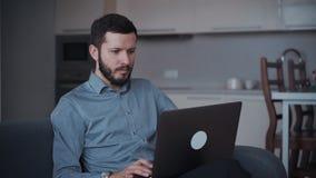 Man som använder den moderna bärbara datorn och hemma arbetar arkivfilmer