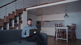 Man som använder den moderna bärbara datorn och hemma arbetar stock video