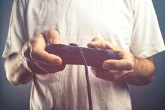 Man som använder den modiga blockkontrollanten för att spela videospel Royaltyfri Bild