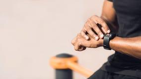 Man som använder den svarta smarta klockan som kontrollerar hjärtahastighet royaltyfri foto