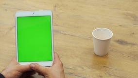 Man som använder den vertikala minnestavlan med den gröna skärmen Närbildskott av händer för man` s med minnestavlan Två i en: 1  lager videofilmer