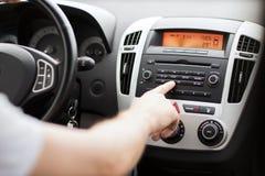 Man som använder det ljudsignal stereo- systemet för bil Arkivbilder