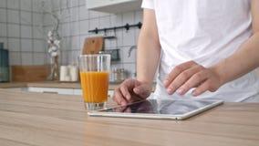 Man som använder elektronisk minnestavlaPC i kök Man som söker matrecept i minnestavladator Slut upp att trycka på för mankock stock video