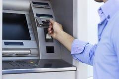Man som använder en ATM Royaltyfria Foton