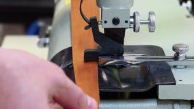 Man som använder en maskin för att inrama kanten av ett läderstycke av material Slapp fokus Hantverk och handgjort begrepp lager videofilmer