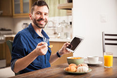 Man som använder en minnestavla över frukosten royaltyfri foto