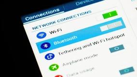 Man som använder fingret för inställning av wifi, av bluetooth och av att tjudra på pekskärmen för ipad för minnestavladatorPC