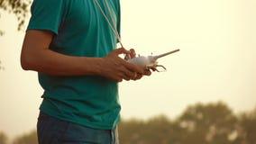 Man som använder fjärrkontrollen för surr RC på solnedgången Fotografering för Bildbyråer