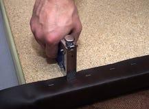 Man som använder handtoolhäftapparaten, och konstläder som stoppar spånskivan arkivbild