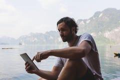 Man som använder hans telefon vid en sjö arkivbilder