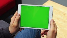 Man som använder horisontalminnestavlan med den gröna skärmen Närbildskott av händer för man` s med minnestavlan Två i en: 1 clos lager videofilmer