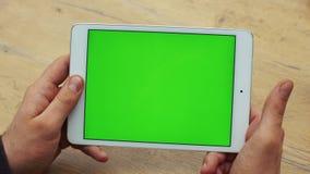 Man som använder horisontalminnestavlan med den gröna skärmen Närbildskott av händer för man` s med minnestavlan Två i en: 1 clos arkivfilmer