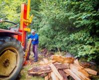 Man som använder journaldelaremaskinen på baksidan av traktoren arkivbild