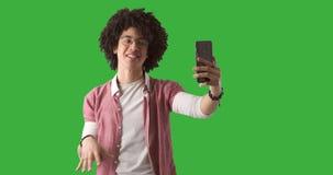 Man som använder mobiltelefonen för den videopd appellen på grön bakgrund stock video