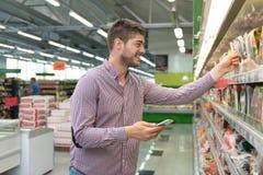 Man som använder mobiltelefonen, medan shoppa i supermarket Royaltyfri Fotografi