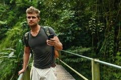 Man som använder mobiltelefonen, Smartphone i natur Lopp turism royaltyfria bilder