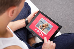 Man som använder online-datera app på minnestavlan royaltyfri foto