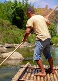 Man som anv?nder polen f?r att segla bambuflotten i floden En av karri?ren f?r turism p? det Chiang Mai landskapet i Thailand Dju arkivbilder