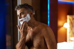 Man som använder raka kräm på framsida i badrum Manhudomsorg Arkivbild