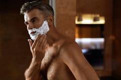 Man som använder raka kräm på framsida i badrum Manhudomsorg royaltyfria foton