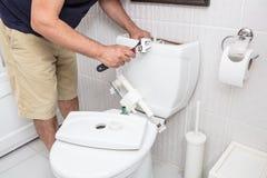 Man som använder skiftnyckeln som reparerar toalettcisternen arkivfoton
