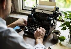 Man som använder skriva den Retro författaren för skrivmaskinsmaskinarbete royaltyfria bilder