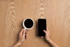 Man som använder smart telefonsammanträde på tabellen, smart telefon för handinnehav Fotografering för Bildbyråer
