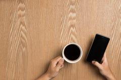 Man som använder smart telefonsammanträde på tabellen, smart telefon för handinnehav Royaltyfri Fotografi