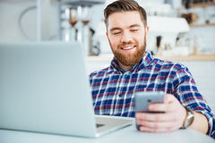 Man som använder smartphone- och bärbar datorcompute i kafé Arkivfoton