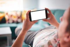 Man som använder smartphonen som är horisontal på soffan royaltyfri fotografi