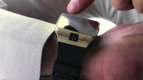 Man som använder smartwatch app med hans finger lager videofilmer