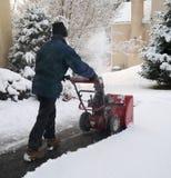 Man som använder snowbloweren under vinterstorm Arkivbild