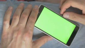 Man som använder telefonen med den gröna skärmen Skjutit på en digital kamera i 4K, så dig kan lätt kantjustera, rotera och zooma stock video