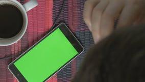 Man som använder telefonen med den gröna skärmen Skjutit på en digital kamera i 4K, så dig kan lätt kantjustera, rotera och zooma lager videofilmer