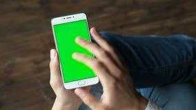Man som använder telefonen med den gröna skärmhållen i händer arkivfilmer