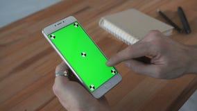 Man som använder telefonen med den gröna skärmhållen i händer lager videofilmer