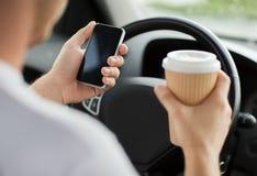 Man som använder telefonen, medan köra bilen Fotografering för Bildbyråer
