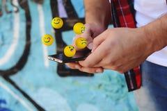 Man som använder telefonen som överför emojis Fotografering för Bildbyråer