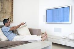 Man som använder TVfjärrkontrollen i vardagsrum Arkivfoto