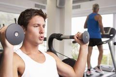 Man som använder viktmaskinen med löparen på trampkvarnen i bakgrund Royaltyfri Foto