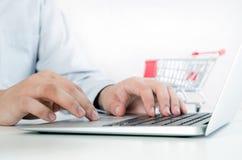 Man som använder bärbara datorn för internetshopping Sammansättning med shoppingspårvagnen Arkivbild