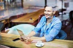 Man som använder den digitala minnestavlan på kafét Fotografering för Bildbyråer